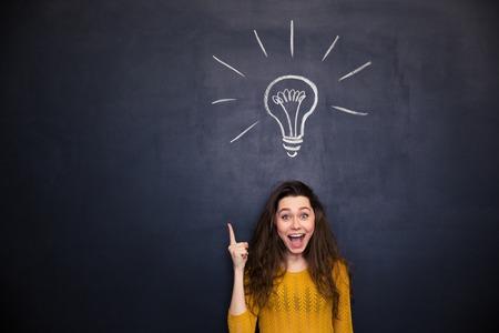 開いた口を上向きと黒板背景にアイデアを持つ陽気な若い女性