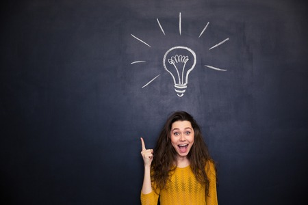 Cheerful young woman with opened mouth pointing up  and having an idea over blackboard background Standard-Bild