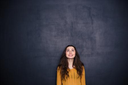mujer joven mirando copyspace sobre fondo negro sonriendo