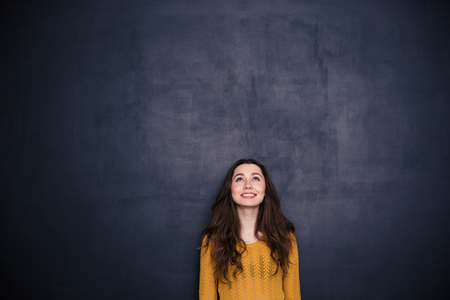 relaxed woman: Smiling young woman looking up at copyspace over black background