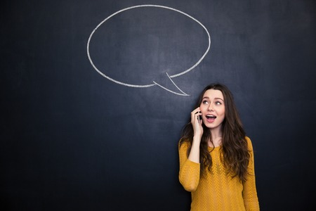 Cheerful cute lovely young woman talking on cell phone over blackboard with blank speech bubble