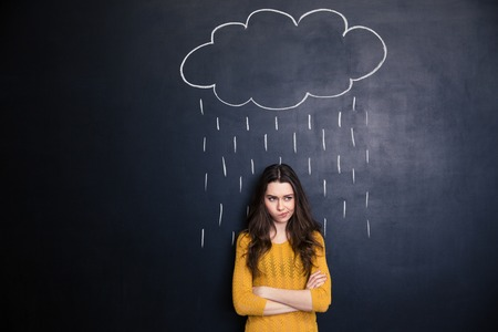 Unpleased young woman with raincloud drawn over her on a blackboard background standing with arms crossed