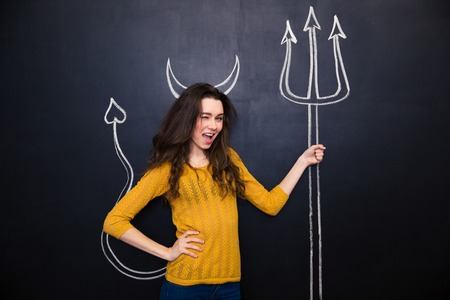 provocative woman: Flirty young woman standing and winking over chalkboard background with drawn devils horns and trident Stock Photo