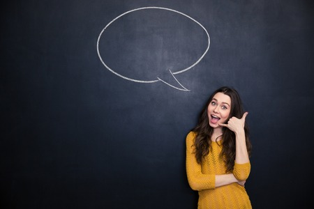 imitating: Happy beautiful young woman gesturing talking on phone and standing on blackboard background with blank speech bubble