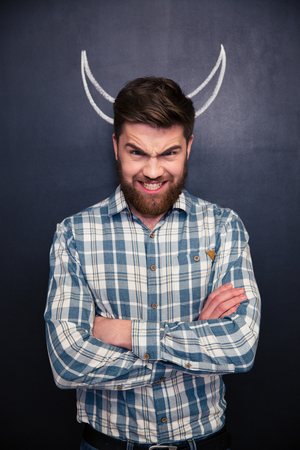 folded hands: Portrait of handsome man pretending devil standing with arms crossed over chalkboard background with drawn horns
