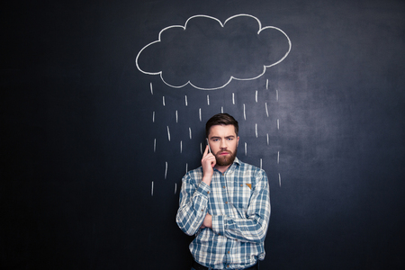 negative: Sad handsome young man with beard talking on mobile phone  under raincloud and rain drawn over him on a blackboard background