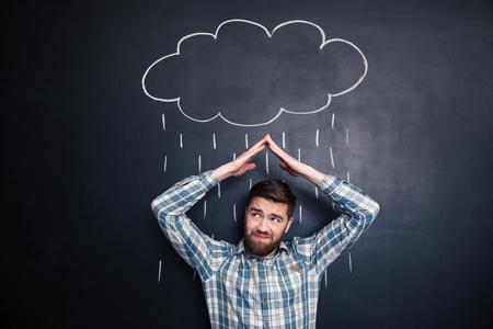 uomo sotto la pioggia: Accigliato irritato giovane in possesso di mani sopra la testa e che copre dalla pioggia tratte da raincloud su sfondo lavagna