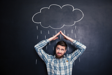 rain cloud: Frowning irritated young man holding hands above head and covering from drawn rain from raincloud over blackboard background Stock Photo