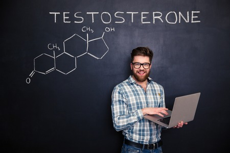 chemical structure: Happy young scientist standing over chemical structure of testosterone molecule drawn on chalkboard background and using laptop Stock Photo