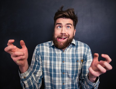 Portrait of ugly bearded young man in checkered shirt grimacing over black background Stock Photo