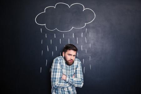 Apuesto hombre con barba de pie sintiendo frío bajo la lluvia dibuja en el fondo de la pizarra Foto de archivo - 51707905