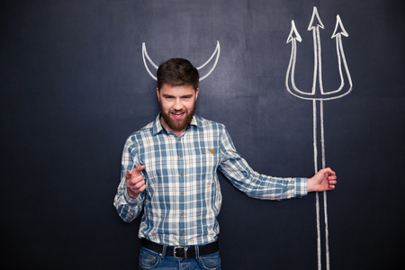 cuernos: Attractive young man with devils horns holding trident and pointing on you over blackboard background