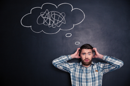 confused face: Confused bearded young man grabbing his head and thinking about problem with black board behind him Stock Photo