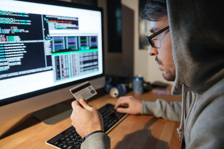 Concentrated young hacker in glasses stealing money from diferent credit cards sitting in dark room Stockfoto