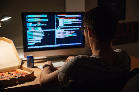 Back view of focused young programmer in glasses writing code and eating pizza