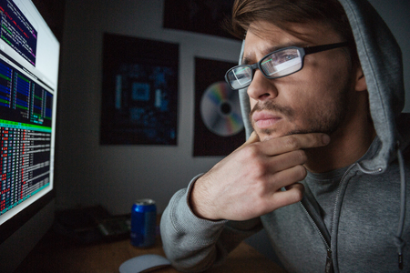pensive man: Pensive attractive young man in glasses and sweatshirt with hood thinking and coding at home Stock Photo