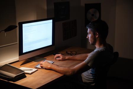 control de calidad: apuesto joven sentado en una habitación oscura y que usa el ordenador