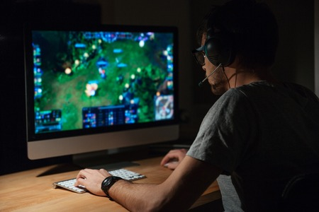 entertainment: Back view of concentrated young gamer in headphones and glasses using computer for playing game at home