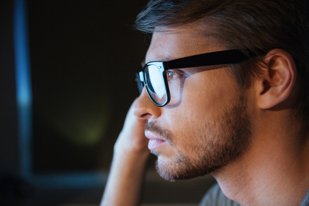 bristle: Profile of thoughtful handsome young man with bristle in glasses sitting and thinking