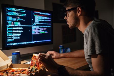 Profiel van geconcentreerde jonge softwareontwikkelaar die thuis pizza en coding eet