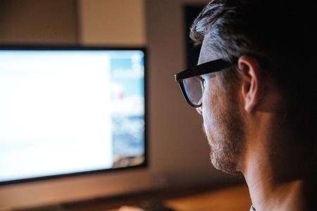 Concentrada se encrespó joven con gafas sentado y mirando la pantalla del monitor de