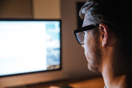 monitors: Concentrated bristled young man in glasses sitting and looking at screen of monitor Stock Photo