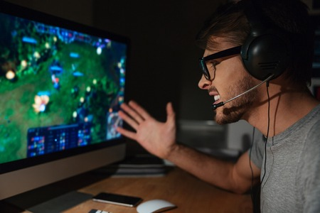 Cheerful young gamer in glasses playing game on computer using headphones