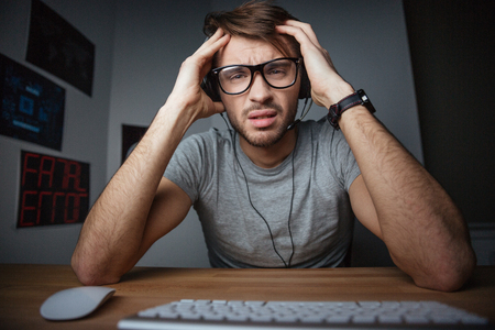 frowning: Frowning young man in earphones and glasses sitting with hands on head in front of computer
