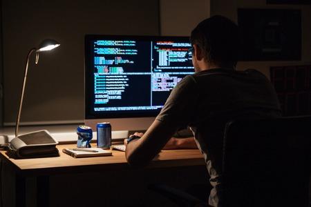 Powrót widok nowoczesnych programista siedzi i pisania kodu w ciemnym pomieszczeniu Zdjęcie Seryjne