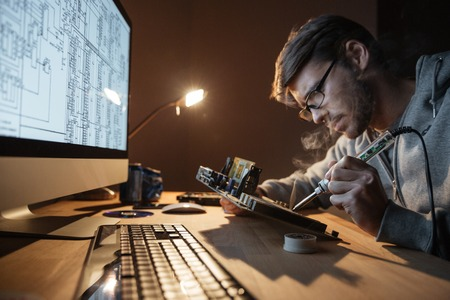 broken strategy: Focused young man in glasses repairing motheboard with soldering iron Stock Photo