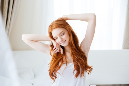 Sensual smiling redhead young woman with long hair sitting and stretching in bed Stock Photo