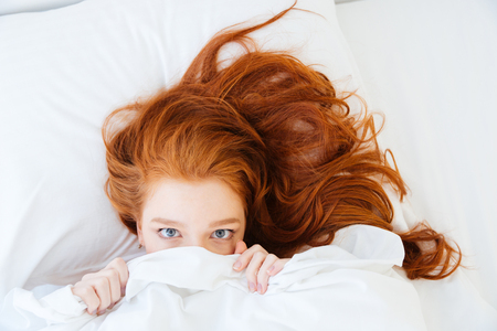 Scared redhead young woman lying in bed and hiding under the sheet