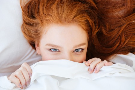 Closeup of cute lovely young woman with red hair lying and hiding under white blanket Stock Photo
