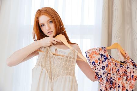 物思いにふける美しい若い女性 desiding 何を着るし、自宅のドレスを選ぶ 写真素材