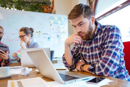 그의 친구들이 함께 공부하는 동안 집중 수염 젊은 남자 노트북을 사용