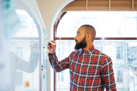 beau jeune homme: Profil d'un homme beau africain avec la barbe debout et l'écriture sur tableau blanc