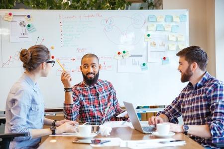 tormenta de ideas: Grupo multiétnico de jóvenes sentados en la sala de conferencias y de intercambio de ideas en reuniones de negocios