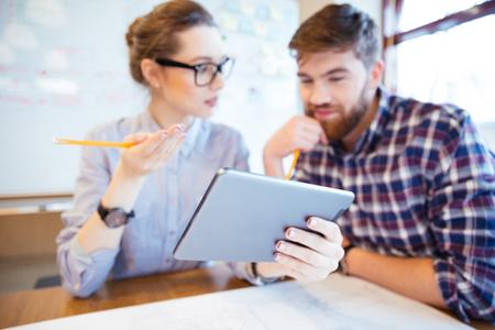 hombres trabajando: Dos hombres de negocios que trabajan con el ordenador tableta en la oficina. Centrarse en la computadora de la tableta