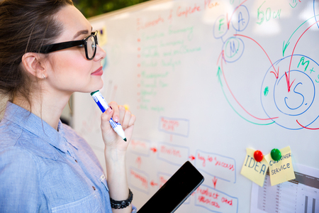 busineswoman: Young busineswoman reading something on whiteboard in office