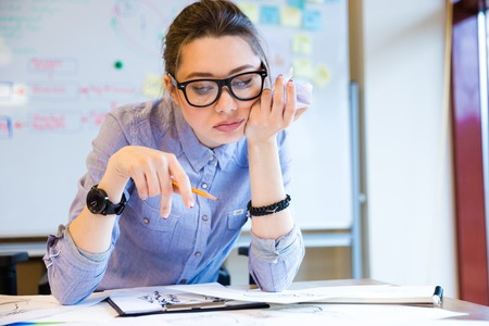 tiredness: Bored pretty young woman fashion designer in glasses working and making sketches in office Stock Photo