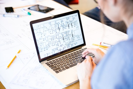 Volver la vista vertical de un ingeniero de la mujer que trabaja en el ordenador portátil con planos en la pantalla en la oficina