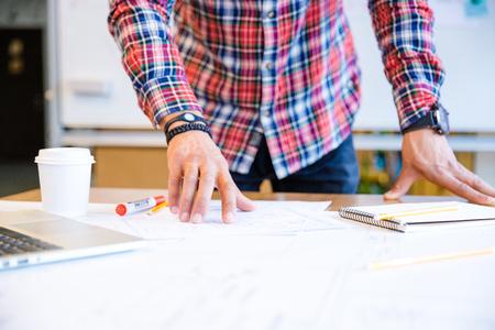 dibujo tecnico: Detalle de las manos del hombre joven afroamericana en cuadros camisa de pie y trabajando en la sala de conferencias Foto de archivo