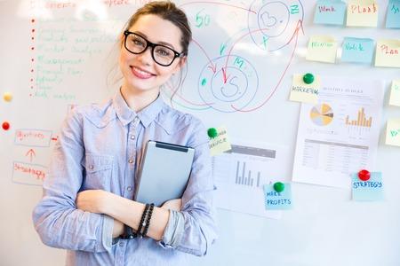 背景にホワイト ボードでカメラを見てメガネの幸せな女性実業家 写真素材