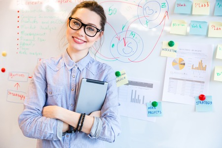 Gelukkig zakenvrouw in glazen te kijken naar de camera met whiteboard op achtergrond