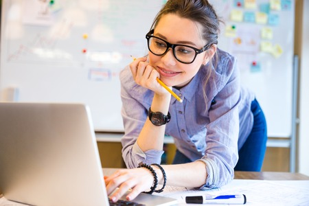 Happy attractive business woman in glasses standing and working with laptop in office