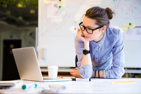 mujer pensativa: Linda encantadora mujer joven estudiante en el estudio de las gafas con ordenador port�til en classrom