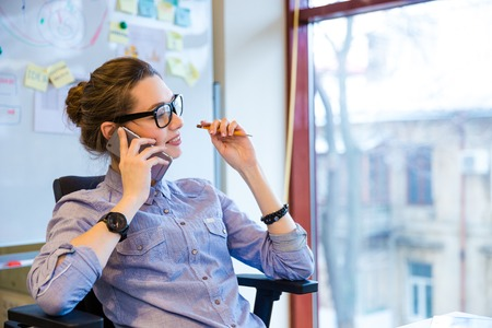 cell phones: Happy beautiful young business woman in glasses sitting and talking on cell phone in office