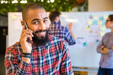 obreros trabajando: Afro estadounidense feliz hablando por tel�fono en la oficina con los colegas en el fondo