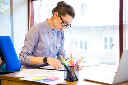 girl wearing glasses: Concentrated pretty young woman fashion designer sitting and drawing sketches in office