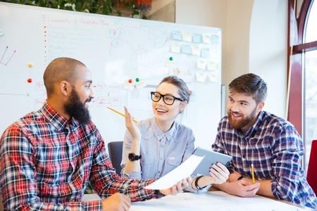 tormenta de ideas: Grupo multiétnico de hombres de negocios felices trabajando juntos en la oficina